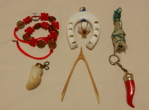 All purchased in the U.S.  Left to right upper row: Taiwanese sacred knotting necklace; Greek horseshoe with garlic bulb; Native American sage.  Bottom row, left to right: rabbit's foot; turkey wishbone; Italian cornu (horn).