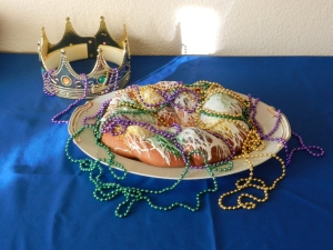 New Orleans King Cake, with Mardi Gras beads decoration and Crown in the background.  © Photo by Mariah Chase, text by Norine Dresser, 2014