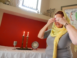 Andrea Dresser covering her eyes as she recites the Sabbath Candle lighting prayer.  Norine Dresser photo collection, 2014.