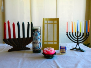 Multicultural ritual candles:  left to right in back: Kwanzaa; Seven African Powers; luminaria; Hanukkah candles.  Foreground, Buddhist lotus candle: Jewish yarhrzeit (memorial) candle.  Norine Dresser photo collection, 2014.