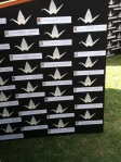 Names of deceased with folded origami crane above each one.  © Norine Dresser photo collection, 2014