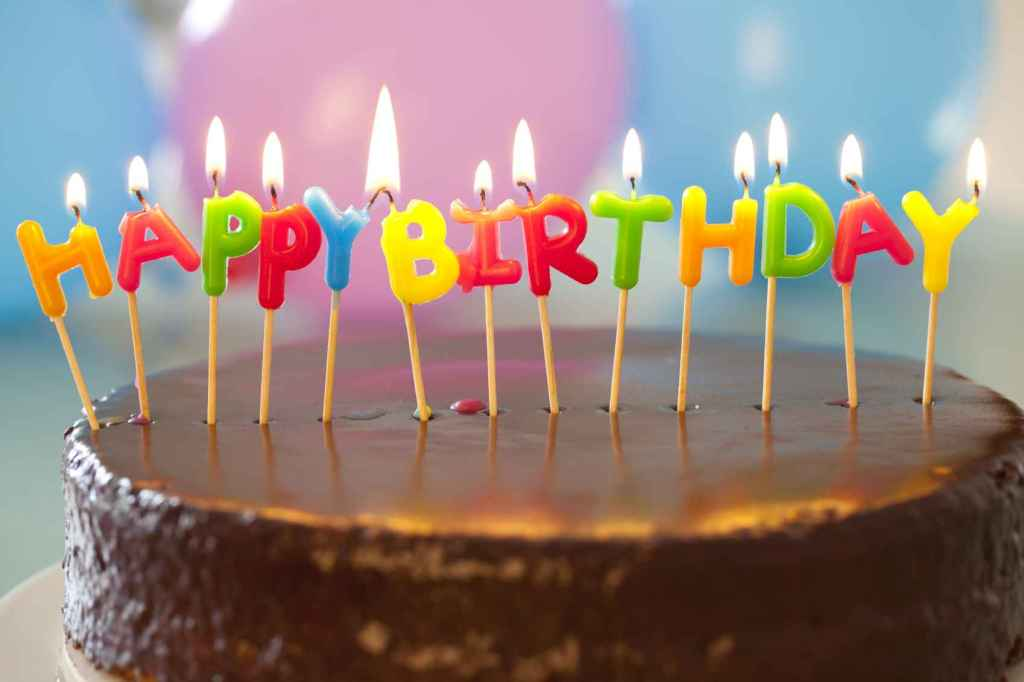 Birthday cake with lit candles.  © Norine Dresser photo collection, 2015.
