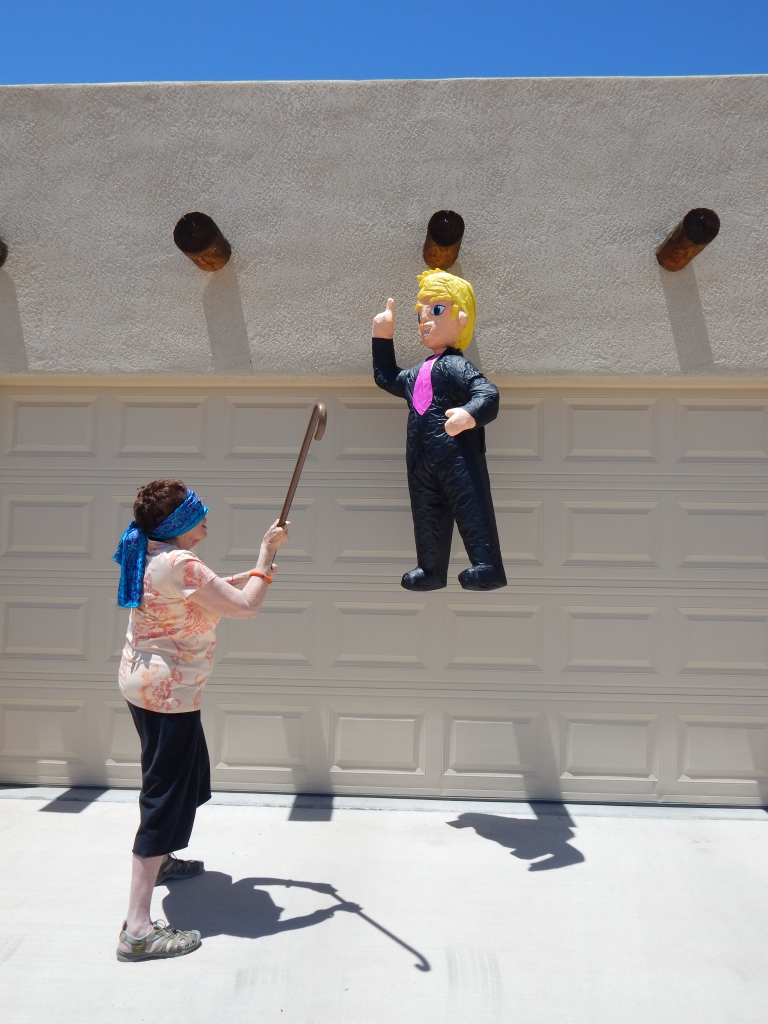 Catharsis! Donald Trump Piñata about to be bashed. Photo by Mariah Chase. Norine Dresser Photo Collection, 2015.