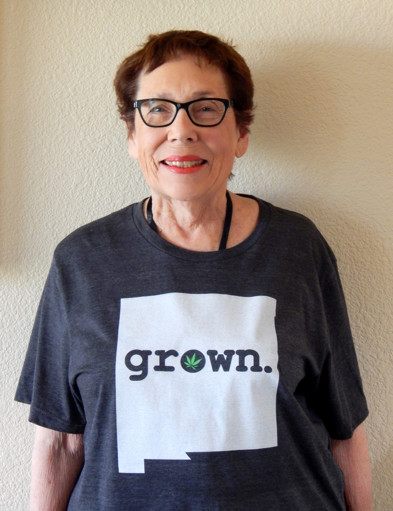 "Norine wearing t-shirt from MJ Expresso. Outline of the state of New Mexico. Indicates that the cannabis is grown in New Mexico. Note the small Marijuana plant in the ""O."" Photo by Mariah Chase. © Norine Dresser photo collection, 2016."