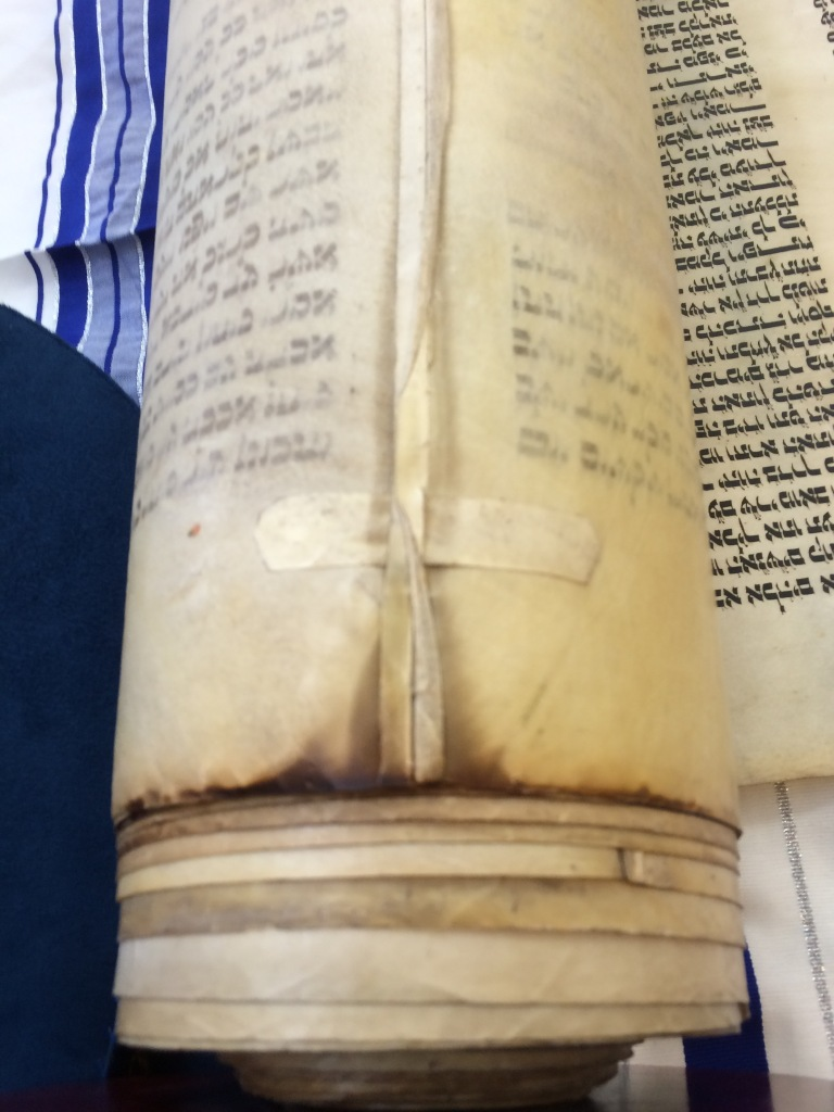 Evidence of the Torah's smokey past. The rabbi invited us to sniff the smoke, but I declined. © Norine Dresser photo collection, 2016.